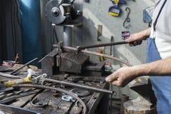 Forgeron faisant le fer travaillé avec la machine industrielle d'équipement de cintreuse pour le recourbement en métal photographie stock libre de droits