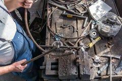 Forgeron faisant le fer travaillé avec la machine industrielle d'équipement de cintreuse pour le recourbement en métal images libres de droits