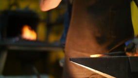 Forgeron Hitting Hot Metal avec un marteau sur une enclume à l'intérieur de son atelier dans le mouvement lent