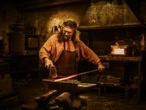 Forgeron supérieur forgeant le métal fondu sur l'enclume dans la forge Photographie stock