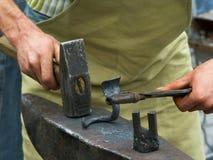 Forgeron travaillant sur un détail en métal Photographie stock libre de droits
