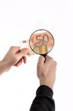Forgery. Man is inspecting a euro banknote with nagnifying glass Stock Images