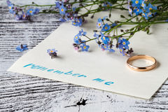 Forget-me-not flower on message note. alone concept Stock Photos