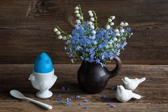 Forget-me-not and lily of the valley's bouquet on wood background, blue egg and birds Stock Photo