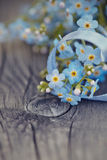 Forget-me-nots with a blue tape on a wooden table Stock Photo