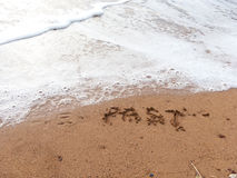 Forget the past. Word Past in handwriting on sandy beach Stock Images