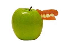 Forget something. Dentures embedded in juicy green apple Royalty Free Stock Photos