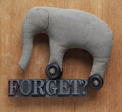 Forget word with old elephant toy. The word forget in old metal type with a homemade, worn, grungy elephant Royalty Free Stock Images