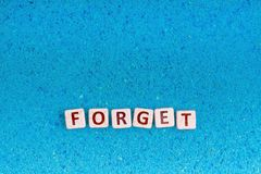 Forget word on stone. Forget word write in square white stone on blue sand, free space for your text royalty free stock photos