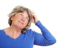 Forgetful ältere Frau stockbild