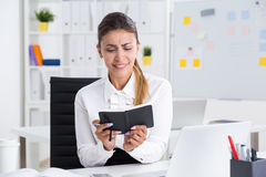 Forgetful business lady. Business lady looking in her notebook in disbelief trying to remember where she had written important meeting details. Concept of rest Royalty Free Stock Images