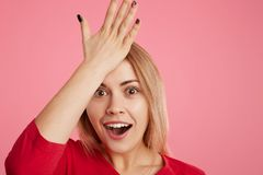Forgetful female model remembers something after long time, keeps hand on forehead, opens mouth in surprisment, remembers to buy p. Resent for friends on coming Stock Images
