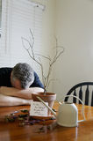 Forgetful Husband. A man with his head down after realizing that he did not water a plant Royalty Free Stock Photo