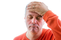 Forgetful man holding his hand to his forehead. With a painstaking expression as he struggles to remember something, head and shoulders on white Stock Images