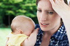 Forgetful Mother Holding Baby Girl At Home. Forgetful Mother Holds Baby Girl At Home Stock Images