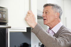 Forgetful Senior Man Looking In Cupboard. Forgetful Senior Man Looks In Cupboard stock image