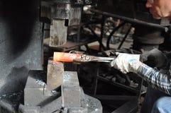 Forgia dell'acciaio rovente in martello pneumatico della forgia fotografie stock