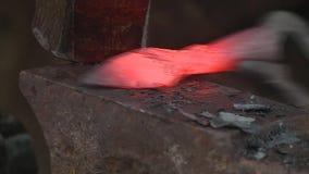 Forging an arrowhead on an anvil. Hammer strikes against the red burning arrowhead on anvil stock video