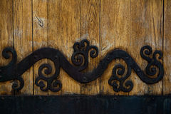 Forging on the door. Ancient forging on the old wooden door Royalty Free Stock Image