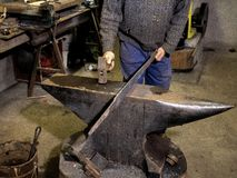 Forging  iron. Blacksmith at work in anvil Stock Image