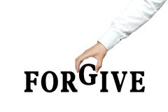 Forgive. Businessman is holding the text of Forgive  on white background Stock Images