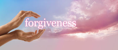 Forgive and release to your Higher Power. Female hands gently cupped around the word FORGIVENESS on a soft blue sky background with a beautiful fluffy pink cloud stock photo