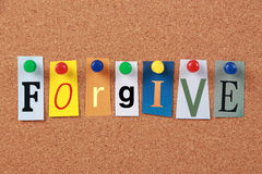 Forgive Single Word. The word Forgive in cut out magazine letters pinned to a corkboard Stock Image