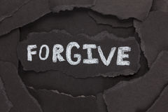 Forgive. Torn pieces of black paper and the word . Close-up Stock Images