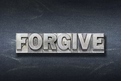 Forgive word den. Forgive word made from metallic letterpress on dark jeans background Stock Image