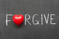 Forgive. Word handwritten on chalkboard with heart symbol instead of O Stock Image