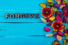 Forgive word on blue wood with flower. Forgive word on old blue color wood with flower and dried flower stock photo