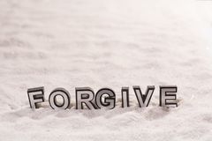 Forgive word on white sand royalty free stock images