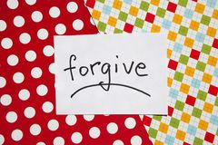 Forgive - word on white real paper with colorful background, relationship concept. Forgive - word on white real paper with colorful background, relationship or royalty free stock photo