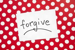 Forgive - word on white real paper with red and dots background, religion and relationship. Concept stock photography