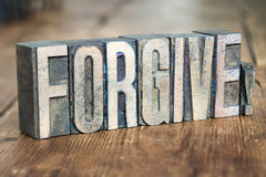 Forgive word wood. Forgive exclamation made from wooden letterpress type on grunge wood Stock Image