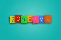 Forgive. The word Forgive written on sticky colored paper Royalty Free Stock Photos