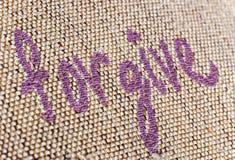 Forgive Writing Macro. Forgive writing sewn on fabric Stock Images