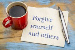 Forgive yourself and others note on napkin. Forgive yourself and others advice - handwriting on a napkin with a cup of coffee Stock Photo