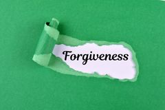 Forgiveness word. The text Forgiveness appearing behind ripped green paper stock image