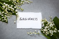 Forgiveness word with white flowers Royalty Free Stock Photography