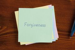 Forgiveness written on a note. Top view of forgiveness written note on the wooden desk with pen aside Royalty Free Stock Photos