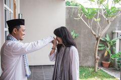 Forgiving and apologizing each other. eid mubarak. Wive shake and kiss her husband`s hand during muslim eid mubarak celebration. forgiving and apologizing each stock images