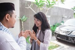 Forgiving and apologizing each other. eid mubarak. Wive shake and kiss her husband`s hand during muslim eid mubarak celebration. forgiving and apologizing each stock photos