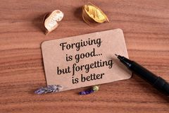 Forgiving is good but forgetting is better. Write in card on wood Stock Photography