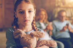 Sad girl waiting for parents to pay attention to her. They forgot about me. Close up shot of a depressed child holding a bunny toy and struggling with ignorance Royalty Free Stock Images
