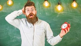 Forgot about time concept. Man with beard and mustache on confused face expression in classroom. Portrait of busy. Nervous young man carrying clock. Negative stock photos