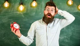 Forgot about time concept. Man with beard and mustache on confused face expression in classroom. Portrait of busy. Nervous young man carrying clock. Negative royalty free stock photos