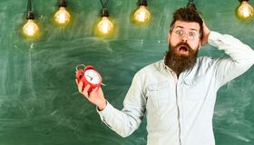 Forgot about time concept. Man with beard and mustache on confused face expression in classroom. Teacher in eyeglasses. Holds alarm clock. Bearded hipster holds stock image