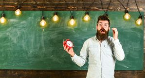 Forgot about time concept. Man with beard and mustache on shocked face in classroom. Teacher in eyeglasses holds alarm. Clock. Bearded hipster holds clock Royalty Free Stock Photos