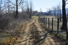 Forgoten country road with barbed wire fence in a beautiful sunny spring day stock photography